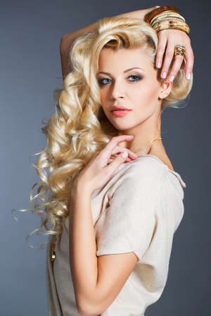 sleeveless dress: Young beautiful woman - blonde, with chic long curly hair, blue eyes, wears a ring on her finger, on the neck - beautiful pendant, and on the hand - bracelets, dressed in a beige sleeveless dress, isolated on gray background.