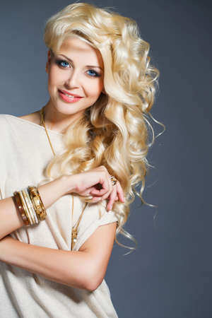 chic woman: Young beautiful woman - blonde, with chic long curly hair, blue eyes, wears a ring on her finger, on the neck - beautiful pendant, and on the hand - bracelets, dressed in a beige sleeveless dress, isolated on gray background.
