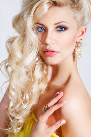chic woman: Young beautiful woman - blonde, with chic long curly hair, blue eyes, beautiful make-up and nail polish, wears a ring on his finger and his ears, beautiful earrings, yellow sleeveless dress, isolated on light gray background.