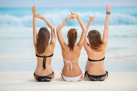 nude butt: summer vacation, holidays, gesture, travel and people concept - group of young women sitting on beach from back. Beautiful Sexy Girls in Bikinis on Tropical Sunny Beach Stock Photo