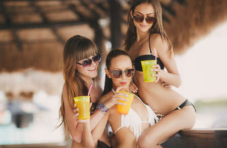 bikini couple: three beautiful sexy women in bikini in bar on Hawaii at beach bar. Beautiful girls enjoying alcoholic beverage cocktail outside. Smiling happy Caucasian women on Hawaiian beach.