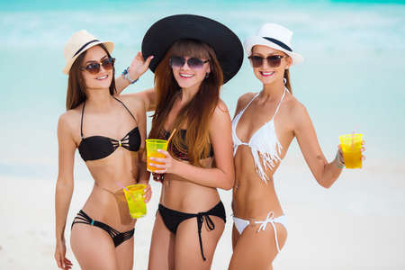 beautiful girls having fun on summer vacation. Three woman lying in the sand on the beach, drinking fancy cocktails and tanning in the sun. young happy people with cocktails in hand on tropical beach photo