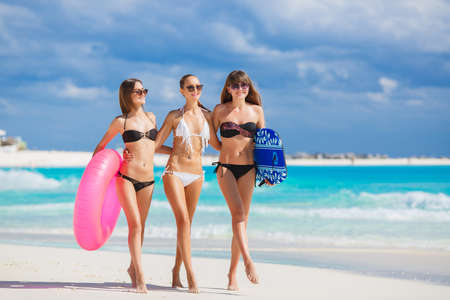 girl friends: Three slim young girls in bikinis on the beach. Group of Three Beautiful Attractive Young Women Walking on the Beach. happy girl friends having fun at the beach while on vacation