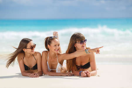 tanned girl: Three slim young girls in bikinis on the beach. summer holidays and vacation - girls in bikinis sunbathing on the beach.