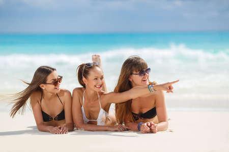 beach girl: Three slim young girls in bikinis on the beach. summer holidays and vacation - girls in bikinis sunbathing on the beach.