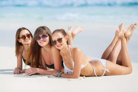 Three slim young girls in bikinis on the beach. summer holidays and vacation - girls in bikinis sunbathing on the beach. photo