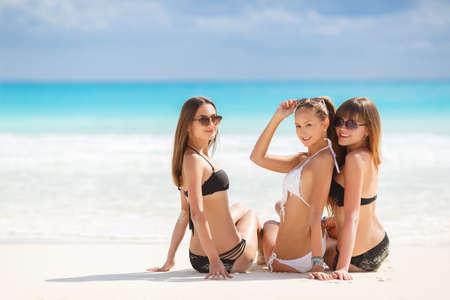 Three slim young girls in bikinis on the beach. summer holidays and vacation - girls in bikinis sunbathing on the beach.