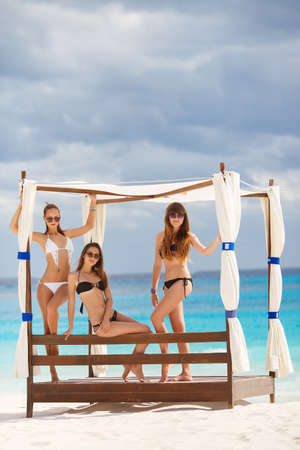 hot teen girl: Three slim young girls in bikinis on the beach. Group of Three Beautiful Attractive Young Women Walking on the Beach. happy girl friends having fun at the beach while on vacation