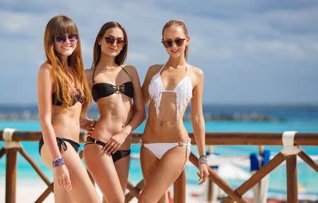 ビーチでビキニで 3 スリムな若い女の子。ビーチの上を歩く 3 つの美しい魅力的な若い女性のグループ。休暇中にビーチで楽しんで幸せのガール フ 写真素材