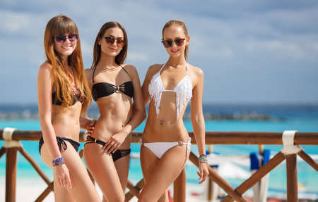 Three slim young girls in bikinis on the beach. Group of Three Beautiful Attractive Young Women Walking on the Beach. happy girl friends having fun at the beach while on vacation