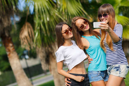 Three young beautiful girls - brunette, long straight hair, in shorts and T-shirts, sun glasses, with a beautiful smile, photographed on a smartphone on a background of tropical greenery. photo