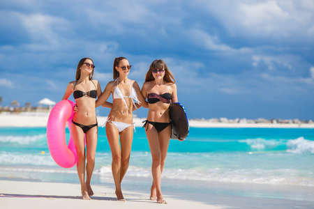 Three slim young girls in bikinis on the beach. Group of Three Beautiful Attractive Young Women Walking on the Beach. happy girl friends having fun at the beach while on vacation photo