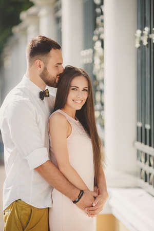 caucasian appearance: A young couple, a man of Caucasian appearance, with short hair and a beautiful beard, white shirt and bow tie and the girl-long-haired brunette in a light pink dress with bare shoulders walking and hugging in the Park in the summer.