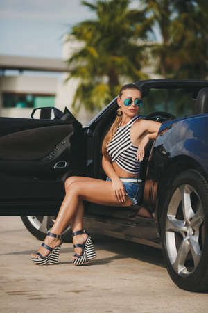 Young lady brunette with long hair gathered behind in the mirror green glasses, wearing earrings in your ears, wearing a striped shirt and a sleeveless blue jean shorts with a white belt, sitting in a parked black convertible photo