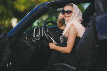 Young lady brunette with long hair, wearing sun glasses, wearing earrings, wearing a black summer dress sleeveless color is clear, pale pink scarf, on the hand-strap black, sitting in a chic black convertible. photo
