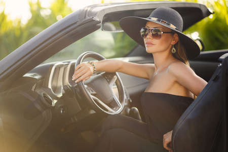 Young lady, brunette with long hair,wearing sun glasses, wearing earrings in the ears is black summer dress sleeveless,head wears a big black hat, on the hand bracelet black,sitting in a chic black convertible. photo