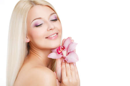 Blue-eyed blonde with long straight hair, beautiful makeup, bare shoulders and beautiful hair, posing for a photograph, holding a flower near the face of pink orchids isolated on white background. photo