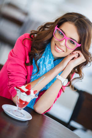 Young beautiful brunette with long curly hair and brown eyes,dressed in a bright pink jacket,blue air scarf and pink glasses,sitting at a table in a cafe with ice cream and strawberries. photo