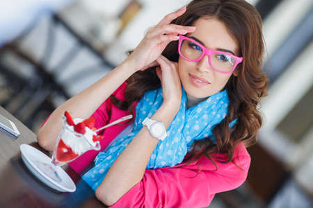 retro lady: Young beautiful brunette with long curly hair and brown eyes,dressed in a bright pink jacket,blue air scarf and pink glasses,sitting at a table in a cafe with ice cream and strawberries. Stock Photo