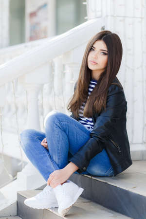 caucasian appearance: Beautiful young girl, Caucasian appearance, with dark, long, straight hair, brown eyes and beautiful dark eyebrows, wearing a striped shirt, jeans and a black leather jacket sitting on the street on the sidewalk near the white railing.
