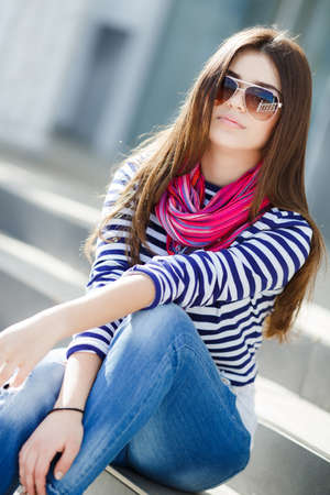 caucasian appearance: Beautiful young girl, Caucasian appearance, with dark, long, straight hair, sun glasses, wearing a striped shirt, jeans wearing pink neck scarf, sitting outdoors on stairs in the city.