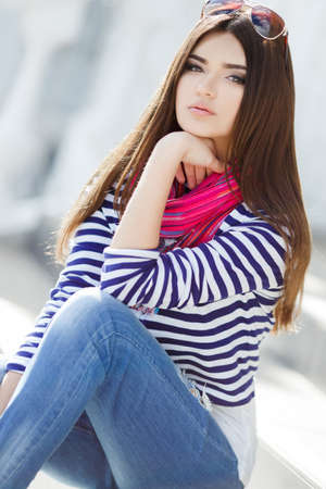 caucasian appearance: Beautiful young girl, Caucasian appearance, with dark, long, straight hair, brown eyes and beautiful dark eyebrows, wearing a striped shirt, blue jeans, wearing pink neck scarf, sitting outdoors on stairs in the city.