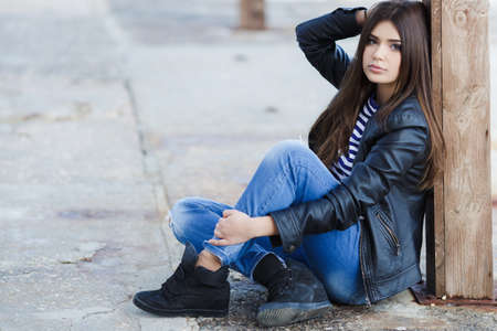 Beautiful young girl, Caucasian appearance, with dark, long, straight hair, brown eyes and beautiful dark eyebrows, wearing a striped shirt, blue jeans and black leather jacket, sitting on the street on the sidewalk