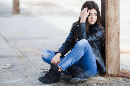 caucasian appearance: Beautiful young girl, Caucasian appearance, with dark, long, straight hair, brown eyes and beautiful dark eyebrows, wearing a striped shirt, blue jeans and black leather jacket, sitting on the street on the sidewalk
