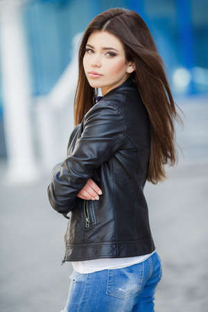 Beautiful fashionable young woman outdoor. glamorous portrait of young beautiful woman in a leather jacket. beautiful girl portrait. Beautiful fashionable woman standing on city street. Fashion Look