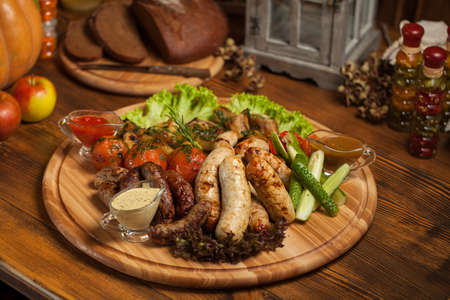 Hearty dinner on a wooden table in a cottage, sausages, grilled with different sauces, herbs, tomatoes, cucumbers, on a round wooden board, apples, pumpkins, bon appetit. photo