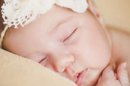 sleep mask: Cute newborn baby boy sleeping on a soft blanket beige color on the forehead of the child-the sleep mask is made in the form of white flowers with bead in the middle of the flower and the soft white rubber band around the head. Stock Photo