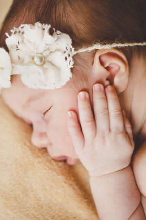 births: Cute newborn baby boy sleeping on a soft blanket beige color on the forehead of the child-the sleep mask is made in the form of white flowers with bead in the middle of the flower and the soft white rubber band around the head. Stock Photo