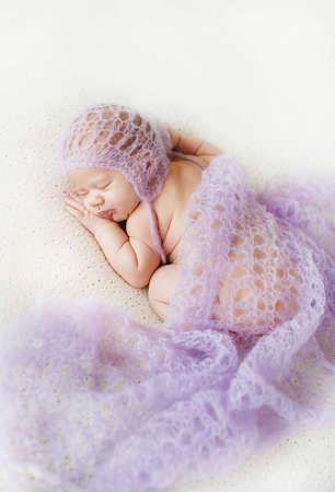 births: Cute newborn baby peacefully sleeping on the white bed,with his hand under his cheek,covered with a knitted blanket pale blue on his head wearing a knitted cap pale blue color. Stock Photo