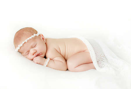 births: Portrait of a newborn baby boy sleeping on a blanket in light gray on his head wearing a crown of large pearls, on the handle wearing a bracelet of white pearls, baby put the pen under the cheek.