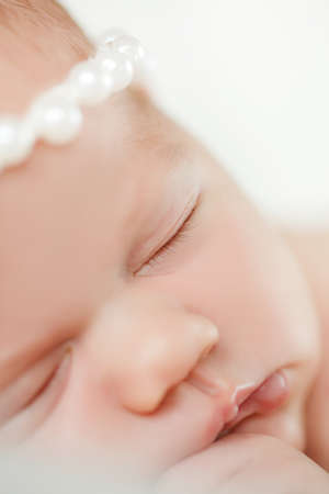 Portrait of a newborn baby boy sleeping on a blanket in light gray on his head wearing a crown of large pearls, on the handle wearing a bracelet of white pearls, baby put the pen under the cheek.