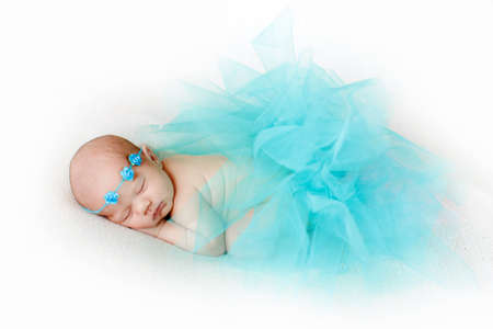 Cute newborn baby sleeping peacefully in white bed, with his hands under his cheek covered with a knitted blanket of pale blue, tied around the head of a blue rope knitted flowers. Stock Photo