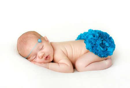 ニット花青いロープの頭の周りに淡いブルーのニット毛布で覆われて彼の頬の下で両手の白いベッドで安らかに眠るかわいい生まれたての赤ん坊が