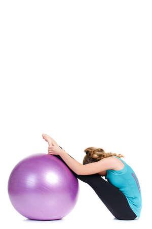 cabelo amarrado: Uma jovem mulher, uma morena de cabelos longos amarrados em um rabo de cavalo, em um t-shirt azul e cal�as pretas, como instrutor, demonstra os exerc�cios de alongamento complexos com uma grande bola de fitness, roxo.