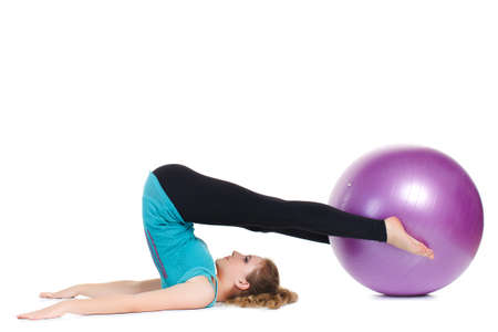 hair tied: A young woman,a brunette with long hair tied in a ponytail,in a blue t-shirt and black pants,as an instructor,demonstrates the complex stretching exercises with a large ball for fitness,purple.
