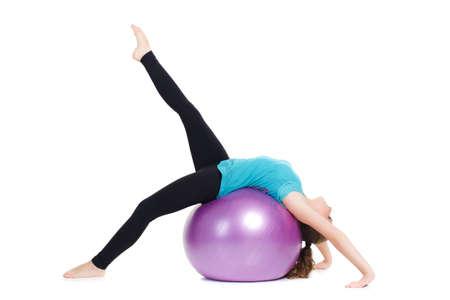cabelo amarrado: Uma jovem mulher, uma morena de cabelos longos amarrados em um rabo de cavalo, em um t-shirt azul e calças pretas, como instrutor, demonstra os exercícios de alongamento complexos com uma grande bola de fitness, roxo.