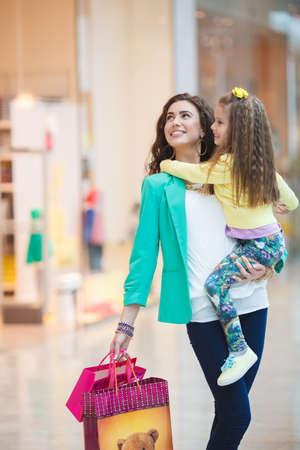 Moeder-jonge brunette met lang krullend haar en bruine ogen, draagt gouden sieraden, armband, oorbel, ring, ketting, gekleed in een groene jas, met een kleine dochter in haar armen, overweegt vitrines een grote supermarkt en winkelen samen.