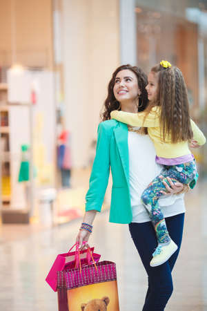 Mother-young brunette with long curly hair and brown eyes,wears gold jewelry,bracelet,earring,ring,necklace,dressed in a green jacket, with a small daughter in her arms ,considering showcases a large supermarket and shopping together.