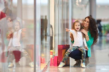 Moeder-jonge brunette met lang krullend haar en bruine ogen, draagt gouden sieraden, armband, oorbel, ring, ketting, gekleed in een groene jas, met een kleine dochter overwegen vitrines een grote supermarkt en winkelen samen.