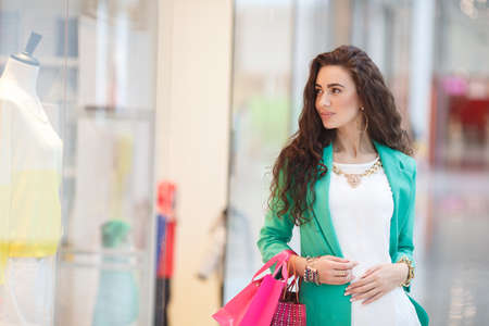 young woman: Young brunette with long curly hair and brown eyes,wears gold jewelry,bracelet,earring,ring,necklace,dressed in a green jacket and black pants,with pink paper bags in his hands,makes shopping in a large supermarket.