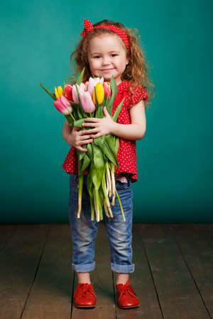 Studio portrait of a pretty little girl child with long curly hair and brown eyes with a large bouquet of tulips in hand, dressed in a red dress with white polka dots, red bandage on his head and blue jeans, isolated on a blue background. photo