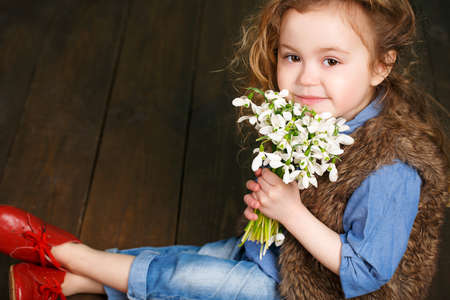Studio portrait of a pretty little girl child with long curly hair and brown eyes with a bouquet of white snowdrops in hand, wearing a blue shirt, brown vest and blue jeans, isolated on a dark background. photo