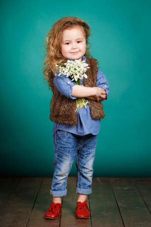 Studio portrait of a pretty little girl child with long curly hair and brown eyes with a bouquet of white snowdrops in hand, dressed in a blue shirt, brown vest and blue jeans, isolated on a blue background. photo