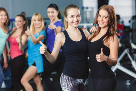 Two happy women in front of group of women in a fitness center holding their thumbs up