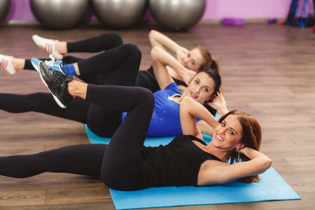 Portrait of fitness class and instructor doing stretching exercise on yoga mats. Group of people in a gym doing aerobics or warming up with gymnastics and stretching exercises Stock Photo