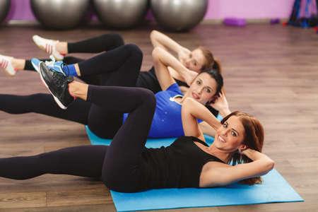 Retrato de clase de fitness e instructor haciendo ejercicios de estiramiento en tapetes de yoga. Grupo de personas en un gimnasio haciendo aeróbic o calentando con gimnasia y ejercicios de estiramiento